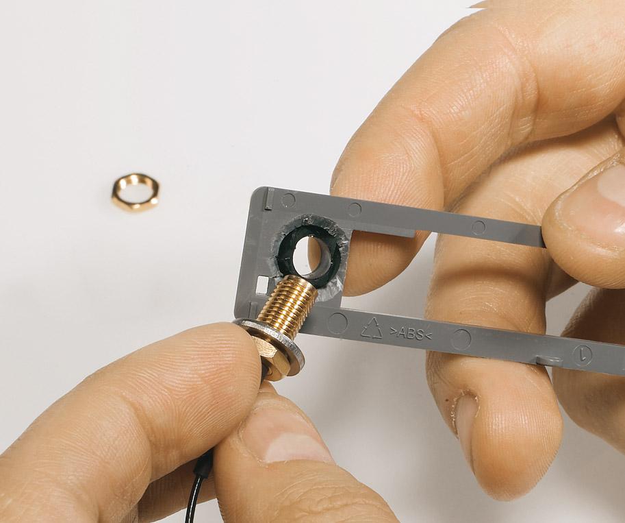 Диаметр переходника составляет 6,5 мм, а отверстия в заглушке (на задней стенке роутера) — 8-10 мм (взависимости от корпуса). Перемычка (при необходимости подгоните ее по размеру) нивелирует эту разницу. Теперь вставьте переходник с шайбой изнутри в отверстие в стенке и закрепите гайкой снаружи.