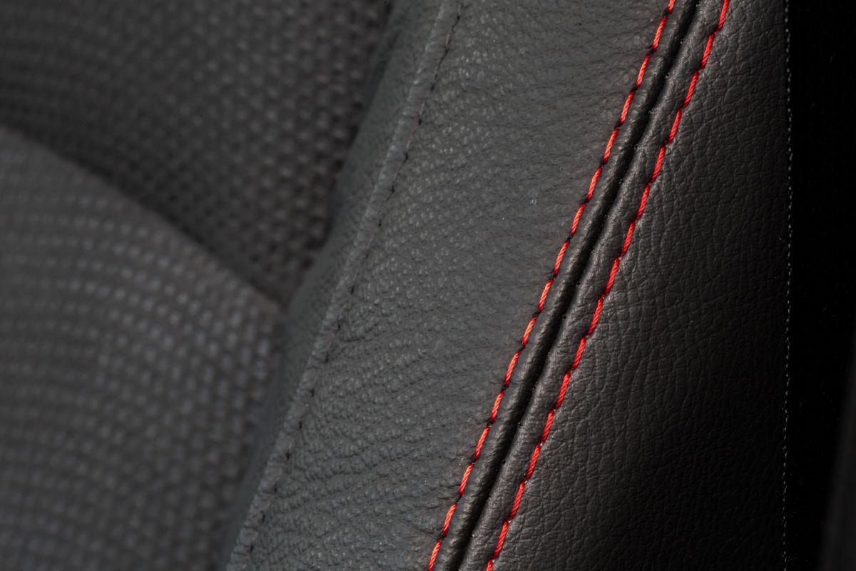 Красная прострочка на сиденьях подчеркивает элегантность салона, оформленного преимущественно в темных тонах. А еще здесь есть подлокотник для водителя и пассажира с вместительным боксом